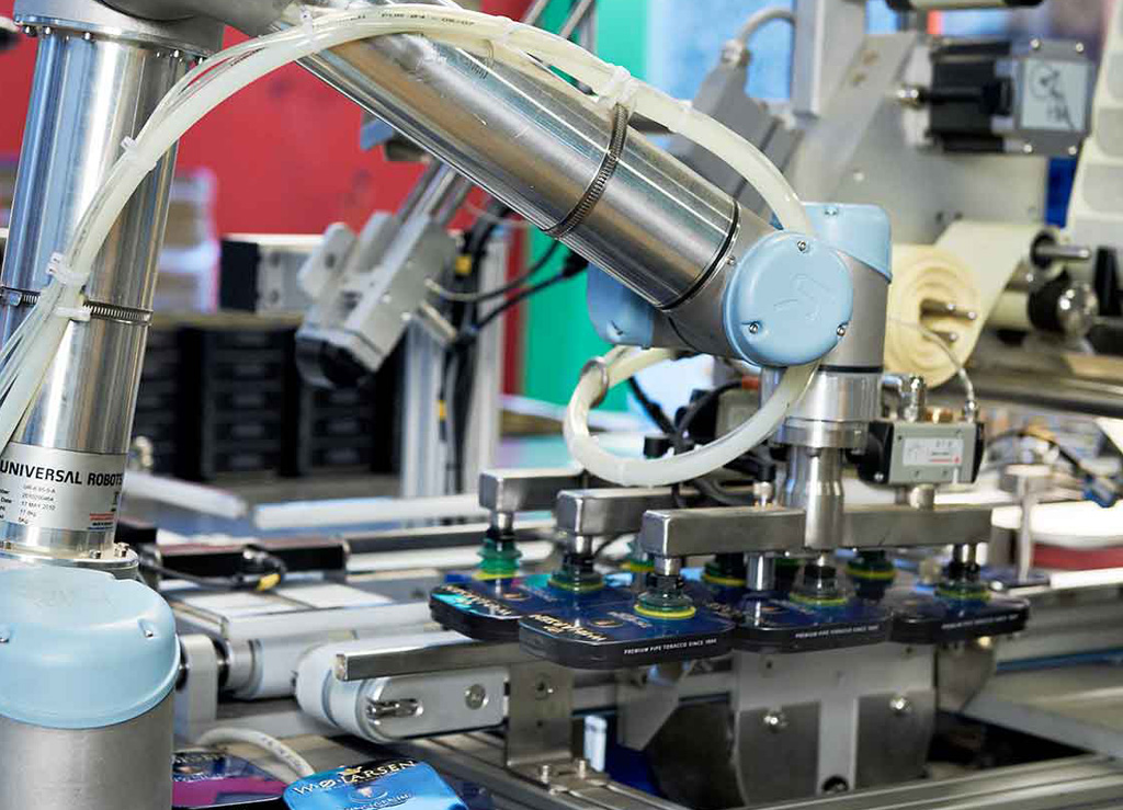 Collaborative robots relieve employees from the strenuous process of preparing bulky packages for large-scale distribution. The added benefit of fenceless-operation allows the robot to work side-by-side with employees on the production lines.